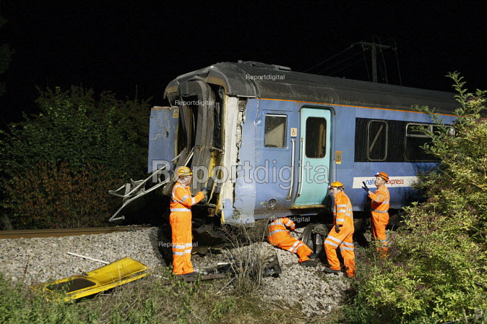 Recovery workers preparing the wreckage of a train to lift it from the tracks. The train and a waste disposal tanker collided at an unmanned level crossing. Little Cornard. Suffolk. - Justin Tallis - 2010-08-18