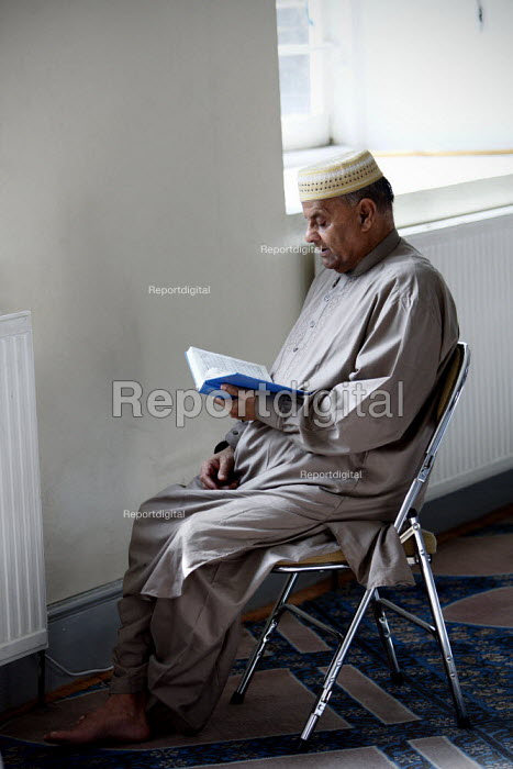 A man reading the Koran during friday prayers at Brick Lane Mosque, East London. - Justin Tallis - 2010-09-03