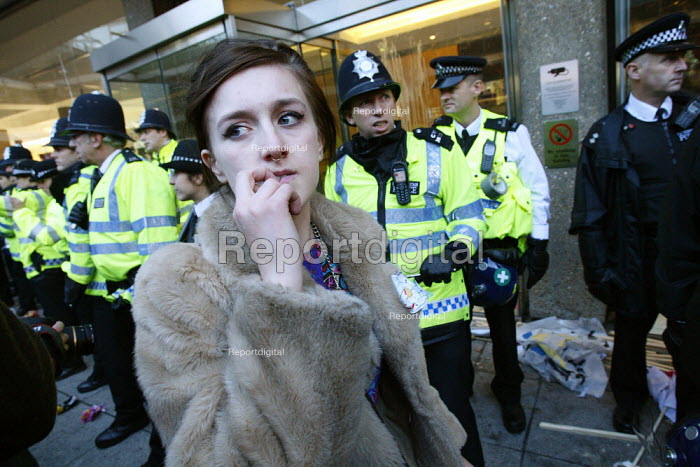 A concerned looking girl walks past police officers as students occupy the ground outside Millbank Tower at a demonstration against plans to raise tuition fees and cuts in university funding. London. - Justin Tallis - 2010-11-10