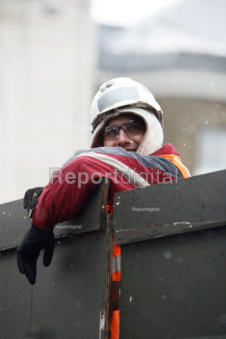 A workman leaning over a temporary wall in the snow. London. - Justin Tallis, JT1011X580.JPG