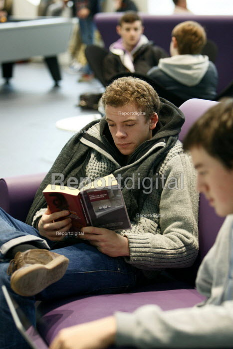 Student trying to read his book during lunch break in The... - Justin Tallis, JT1012046.JPG