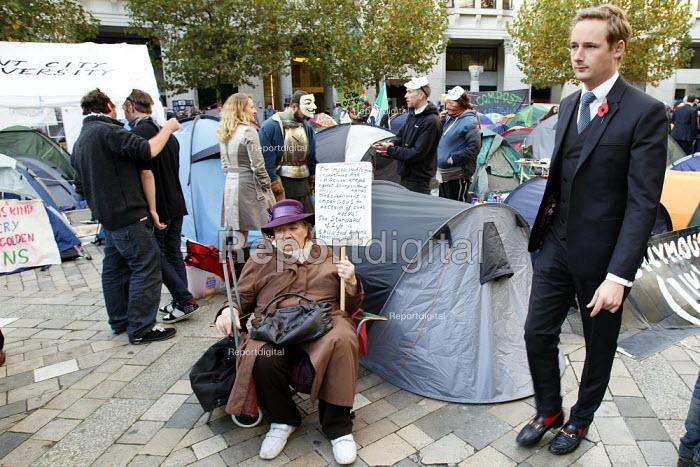 A businessman walking through Occupy London Stock Exchange. St Paul's, London. - Justin Tallis - 2011-11-01