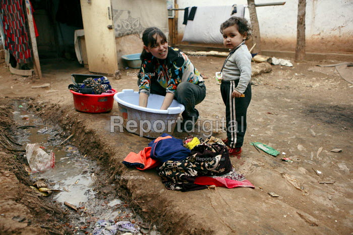 A woman washing her familys clothes. An impoverished Roma Gypsy community that has no running water, therefore community sanitation is of an awful standard and infections along with illnesses are rife. Situated in the town of Jibou, in Romania. - Justin Tallis - 2007-03-17