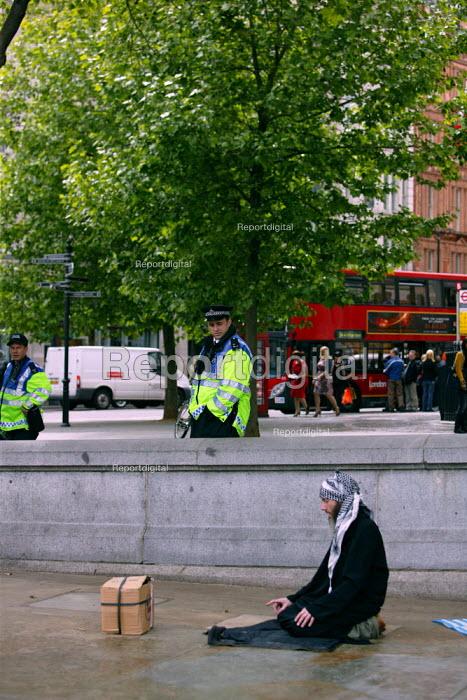 Muslim man praying, facing Mecca, in Trafalgar Square. Police Forward Intelligence officers (FIT) stands close by watching. London. - Justin Tallis - 2009-05-16