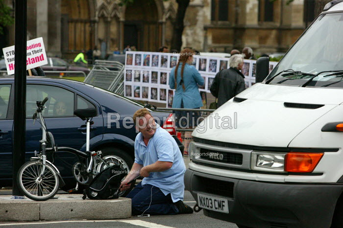 A man laughing as he pumps up a flat tire in the middle of the road. RMT tube strike, London. - Justin Tallis - 2009-06-10