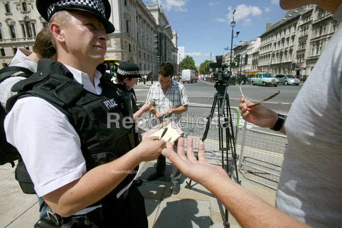 Diplomatic police officers perform a section 44 Stop and Account on an Iranian journalist filming in Parliament Square. London. - Justin Tallis - 2009-06-24