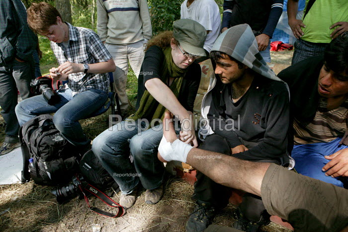 Press photographer Jess Hurd helping a man with an open wound. Refugees from the war in Afghanistan shelter in the Jungle refugee camp, woods in Calais where they are forced to sleep rough. France. - Justin Tallis - 2009-06-27