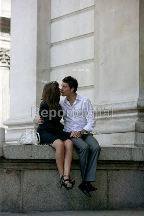 Man and woman enjoying lots of kissing on a wall in the city. London. - Justin Tallis - 2009-08-26