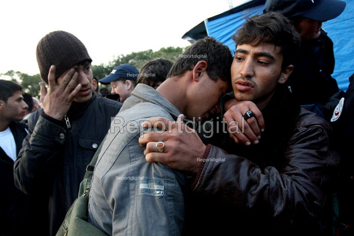 Refugees predominantly from Afghanistan wait surrounded by police before they are removed from their makeshift shelters,, known as the jungle, by French police. Calais, France. - Justin Tallis - 2009-09-22