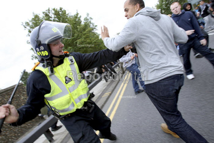 Riot policeman hits a Muslim man after scuffles broke out with far right English Defence League demonstrators. Near Harrow Mosque. London. - Justin Tallis - 2009-09-11