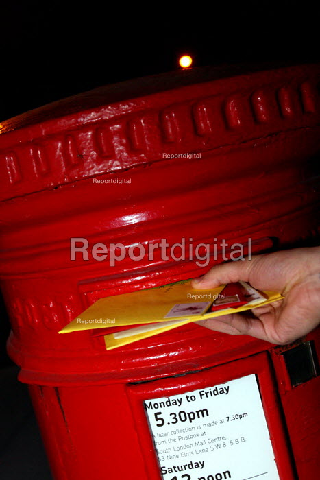 Posting a letter in a postbox at night. London. - Justin Tallis - 2009-10-20