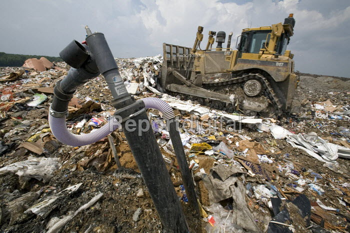 Marshall, Michigan - A well collects methane gas from decaying garbage at the C&C Landfill. The methane is used by Gas Recovery Systems to generate electricity for distribution by Consumers Energy. In the background, a bulldozer levels newly-arrived garbage. - Jim West - 2007-06-27