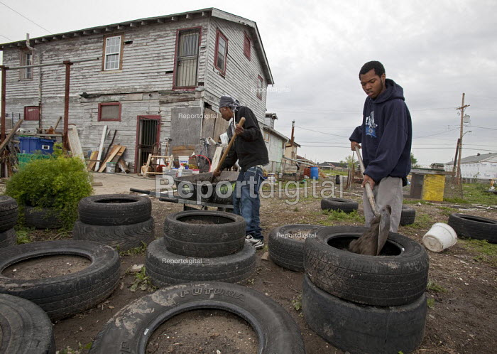 New Orleans, Louisiana - Young people create a community garden in the lower ninth ward. They are placing soil in old tires where they will grow potatoes. Their hope is to turn vacant lots devastated by Hurricane Katrina into an urban farm that will provide learning opportunities for area youth and fresh produce for the neighborhood. - Jim West - 2009-04-01