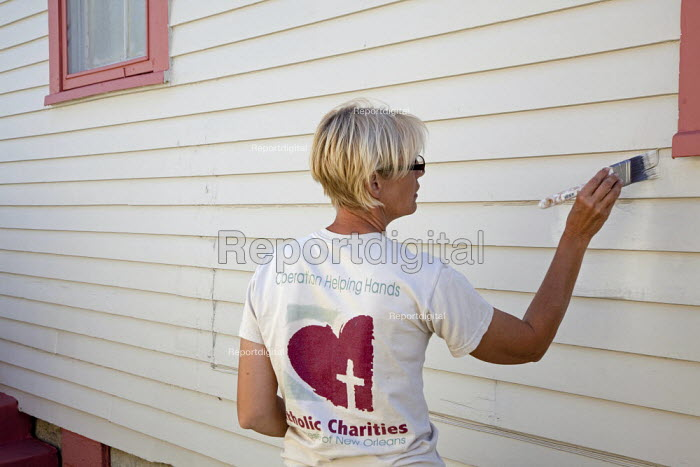 New Orleans, Louisiana - Kay Conroy, a professional painter from Illinois, volunteers her time to paint homes damaged by Hurricane Katrina. Her work is organized through Catholic Charities. Here she touches up work done by a crew of student volunteers. - Jim West - 2009-04-03