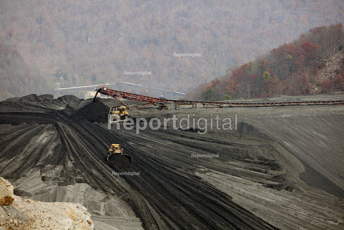 Sylvester, West Virginia USA- Bulldozers spread coal sludge on a coal impoundment dam at Massey Energys Elk Run complex. Impoundments hold liquid and solid wastes from the coal mining process, including toxic chemicals that can seep into local water supplies. - Jim West - 2009-11-09