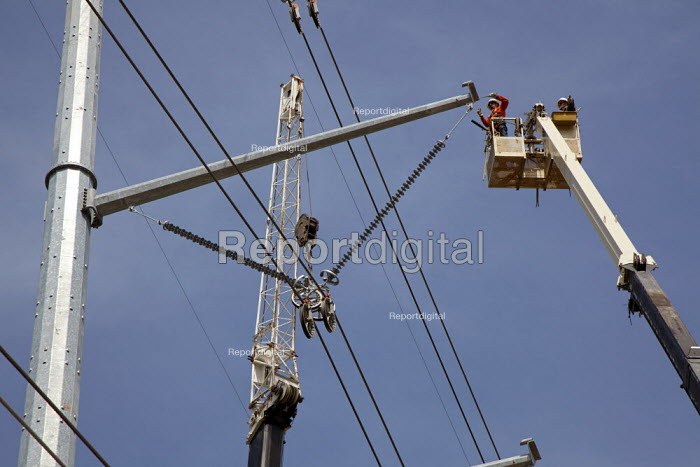 Electricity engineers installing a high voltage power line using a mobile lift platform. - Jim West - 2010-04-20