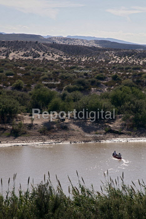 Mexicans cross the Rio Grande in a canoe. The river separates the USA and Mexico. Mexicans illegally cross the river to sell handicrafts to tourists despite threats by U.S. immigration authorities to prosecute tourists who buy. USA - Jim West - 2010-10-12