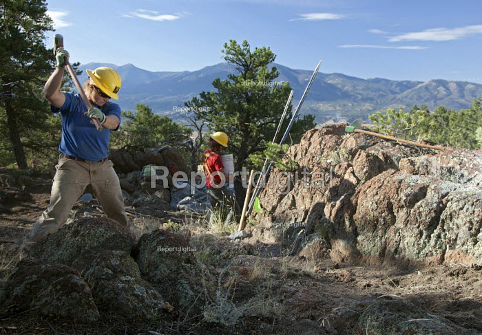A women breaking rocks with a sledgehammer. A crew of volunteers from the Southwest Conservation Corps working on a project to construct a mountain bike trail on land administered by the U.S. Bureau of Land Management. Colorado, USA - Jim West - 2010-10-04