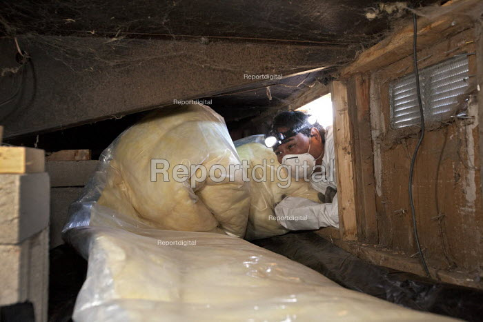 A worker with Veterans Green Jobs installs insulation in the crawl space below a mobile home. With a grant from the state of Colorado, Veterans Green Jobs does free insulating work in the homes of low-income residents of the San Luis Valley. USA - Jim West - 2010-10-06