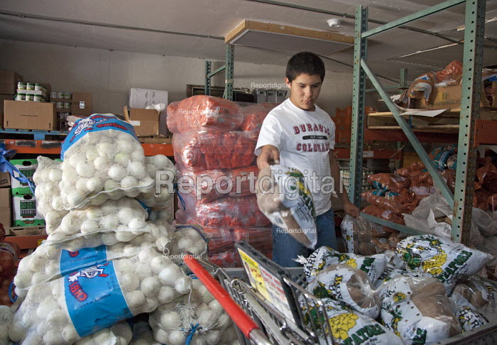 A teenager stacks donated potatoes at a food bank operated by La Puente. USA - Jim West - 2010-10-07