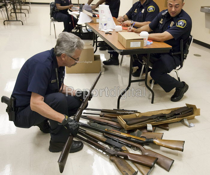 Detroit, Michigan - Police officers examine weapons turned in by residents in a gun buyback program. People were paid $25 to $200, depending on the type and quantity of weapons turned in. - Jim West - 2011-08-30