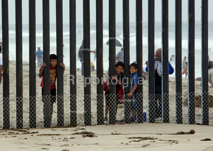 San Ysidro, California, children looking through the fence at Border Field State Park separating the USA and Mexico at a beach at the Pacific Ocean - Jim West - 2011-07-03