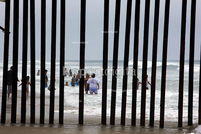 San Ysidro, California, the fence at Border Field State Park separating the USA and Mexico at a beach at the Pacific Ocean. Across the border, Mexican families play in the surf. - Jim West - 2011-07-03