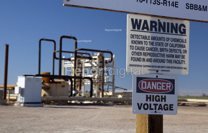 A sign warning of cancer, birth defects and other reproductive harm-causing chemicals, and high voltage electricity at a well for a geothermal energy plant operated by Ormat Technologies, Imperial Valley, California. The pipes carry hot water or steam from deep underground, which is used to generate electricity. USA. - Jim West - 2012-01-28