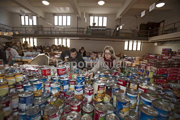 Volunteers sorting donated tinned food which will be distributed to low-income families for Thanksgiving. The annual food distribution is organized by Lighthouse of Oakland County, a social services agency. USA. - Jim West - 2011-11-18