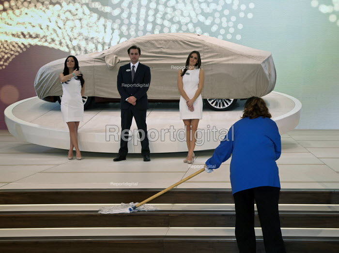 A cleaner mopping the floor as models stand by a new 2013 Lincoln MKZ concept car model before its preview unveiling at the North American International Auto Show. USA. - Jim West - 2012-01-09