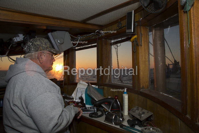 Mobile, Alabama - A shrimp trawler on Mobile Bay. Jackie Schwartz in the wheelhouse of the 52-foot Captain at sunrise. The trawler is part of the Alabama Fisheries Cooperative. - Jim West - 2012-11-08