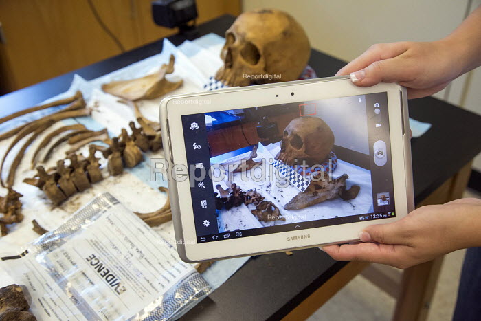 Waco, Texas - A student uses a tablet to photograph what was found of one body. Forensic scientist Dr. Lori Baker and her students at Baylor University try to identify the remains of unidentified migrants who died trying to enter the USA without legal documents. Most perished in a long, hot walk as they tried to evade a Border Patrol checkpoint 70 miles north of the border. Dr Baker is director of Reuniting Families, an effort to identify and repatriate to families the remains of undocumented immigrants that die crossing the southern US border - Jim West - 2013-07-19
