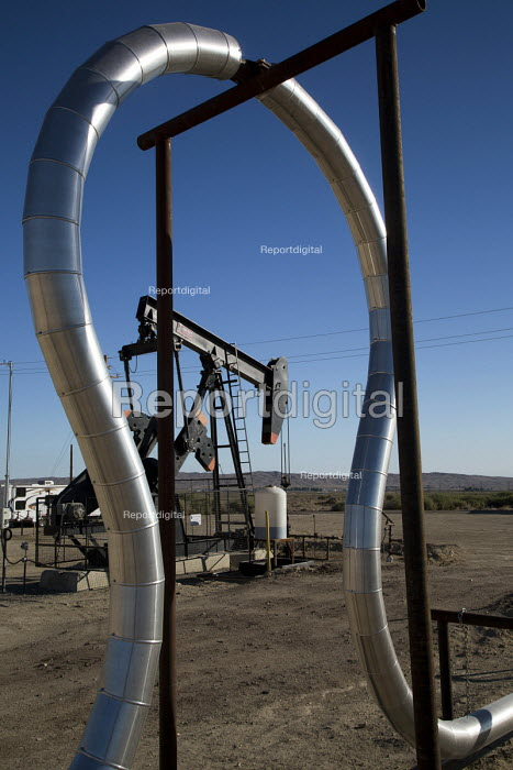 Taft, California - An expansion loop in a natural gas pipeline frames an oil well in the oil and gas fields of southern San Joaquin Valley. - Jim West - 2012-06-24