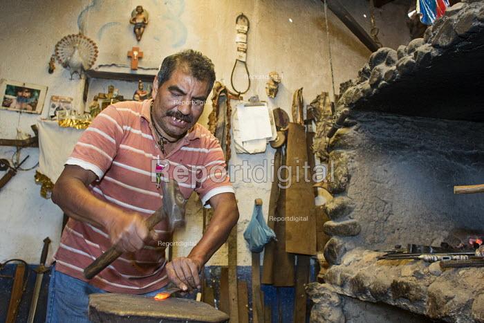 Ocotlan de Morelos, Oaxaca, Mexico - Apolinar Aguilar Velasco makes swords and knives by hand in his workshop. - Jim West - 2015-01-16