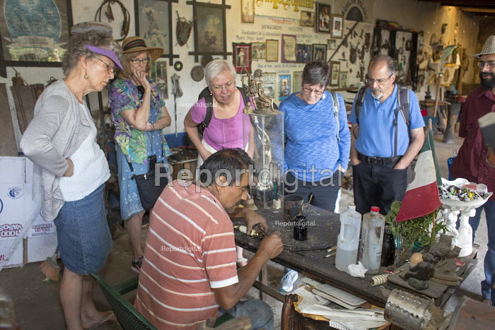 Ocotlan de Morelos, Oaxaca, Mexico - American tourists watch as Apolinar Aguilar Velasco engraves the blade of a hand-made knife in his workshop. - Jim West - 2015-01-16