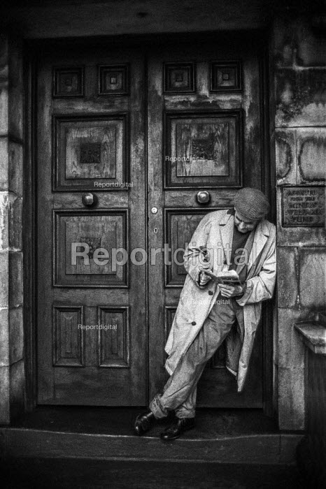 Unemployed man in Blackwood, South Wales reading in doorway next to sign saying Assisted from the Miners Welfare Fund during 1972 strike - Martin Mayer - 1972-01-21