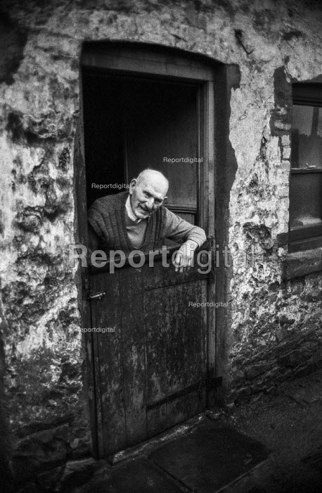 Retired miner Charles Clark, 90, at the doorway of thje last inhabited cottage in row of old National Coal Board cottages, Blackwood, South Wales. He had lived there since 1914 and had taken part in the 1926 General Strike - Martin Mayer - 1972-01-15