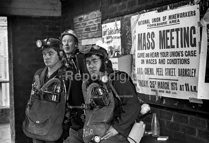 Exhausted miners rescue crew waiting to return down the pit to attempt a further rescue of trapped miners in the flooded Lofthouse colliery next to a poster advertising a union mass meeting about wages and conditions. - Martin Mayer - 1973-03-23