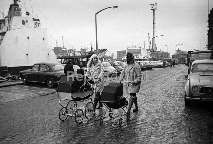 Two young mothers walk through the docks in Hull with headscarves and traditional prams - Martin Mayer - 1968-10-29