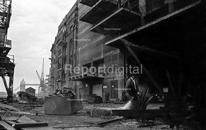 A workman breaks up a crane outside Chamberlains Wharf, near Tower Bridge, London during closure of the old London docks due to containerisation - Martin Mayer - 1987-10-06