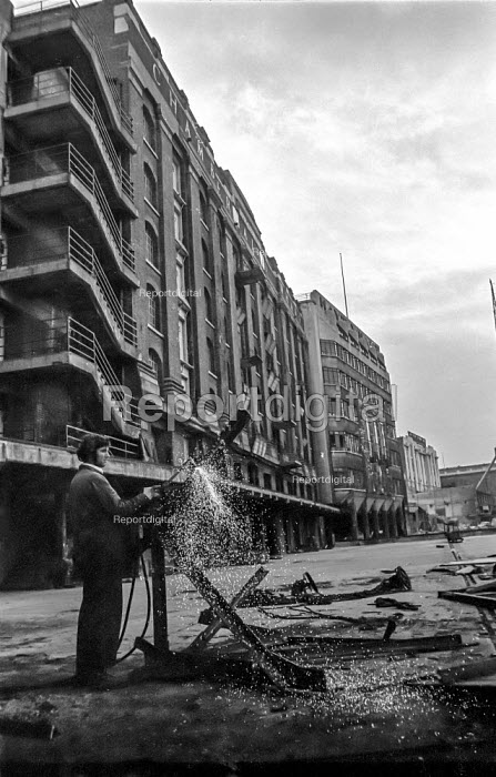 A demolition worker cuts up a crane outside Chamberlains Wharf, next to Hays Wharf, near Tower Bridge during the closure of the old London docks caused by containerisation - Martin Mayer - 1987-10-06