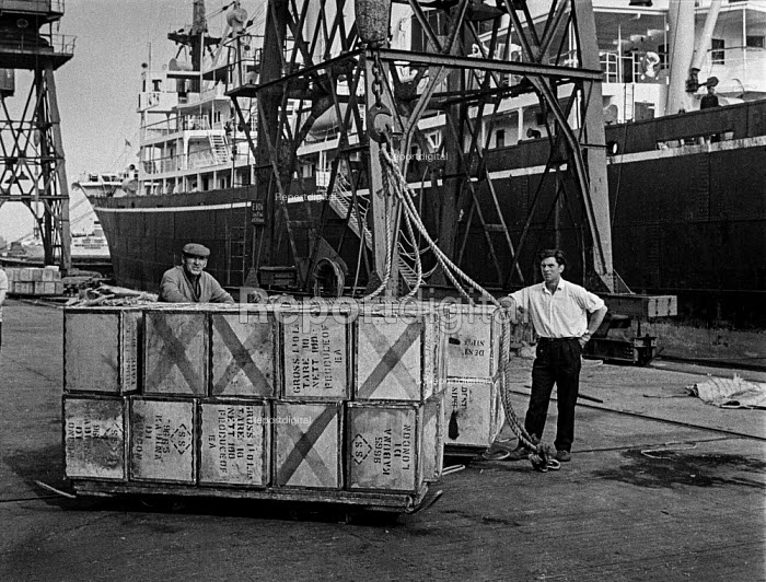 Dock work as it used to be, East India dock, London, before containerisation - a small ship, a crane, ropes, piecemeal cargo and lots of dockers - Martin Mayer - 1970-07-07