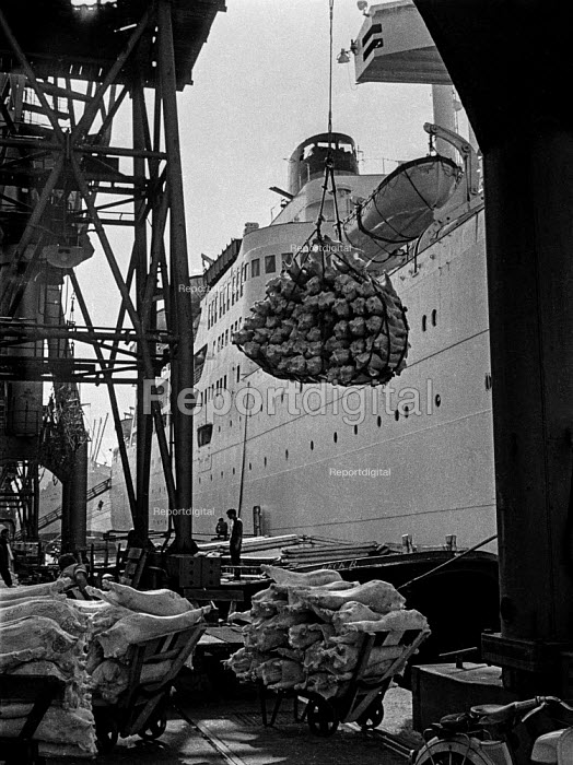 Dock work as it used to be, East India dock, London, before containerisation - a small ship, a crane, ropes, piecemeal cargo and lots of dockers. - Martin Mayer - 1970-07-07