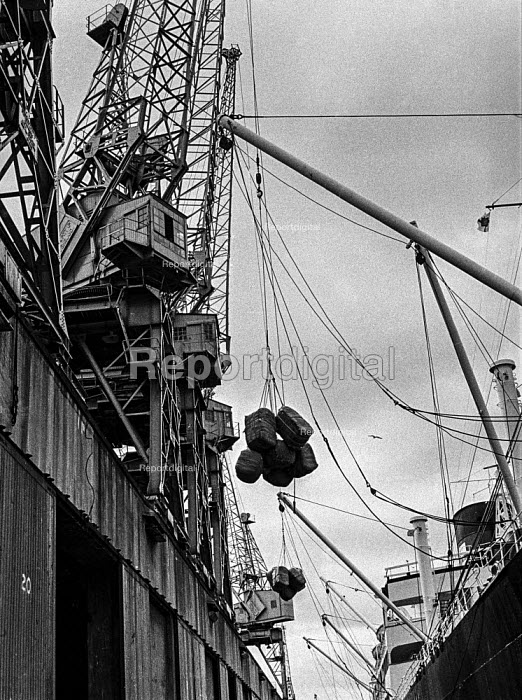 Dock work as it used to be, East India dock, London, before containerisation before containerisation - a small ship, a crane, ropes, piecemeal cargo and lots of dockers. - Martin Mayer - 1970-07-06