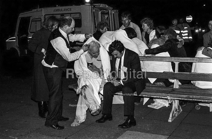 IRA Bombing of The Grand Hotel, Brighton. Hotel staff helping a guest and a journalist interviewing shocked and bloodied delegates to the Conservative Party conference gather outside The Grand Hotel, Brighton, after the IRA exploded a bomb in an attempt to assassinate Margaret Thatcher. - Martin Mayer - 1984-10-12