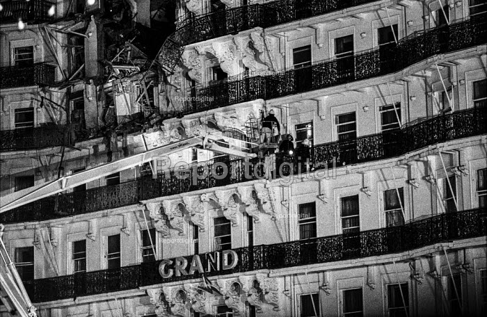 Bomb damage is clearly visible as firemen check for injured guests at the Grand Hotel, Brighton, in the aftermath of the bomb attack in which the IRA attampted to assassinate Prime Minister Matgaret Thatcher - Martin Mayer - 1984-10-12