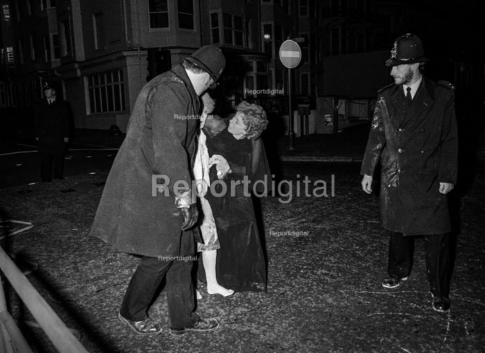 Police help a guest caught in the bomb blast at the Grand Hotel, Brighton, which the IRA detonated with the aim of assassinating Prime Ministe Margaret Thatcher - Martin Mayer - 1984-10-12