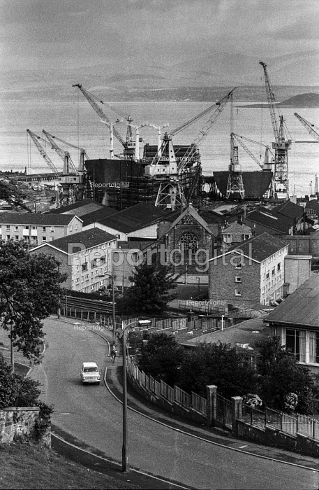 The Scott Lithgow shipyard towers over the local church and housing in Port Glasgow - Martin Mayer - 1971-08-08