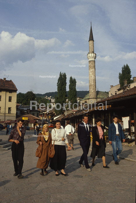 Walking through Sarajevo Old Town, Bosnia, with The Gazi Husrev-bey Mosque behind the market. Muslim headscaves were less common then. - Martin Mayer - 1990-09-07