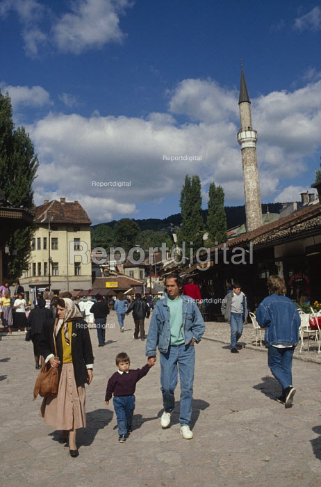 Young family walking through Sarajevo Old Town, Bosnia, with The Gazi Husrev-bey Mosque behind the market. Muslim headscarves were less common then. - Martin Mayer - 1990-09-07